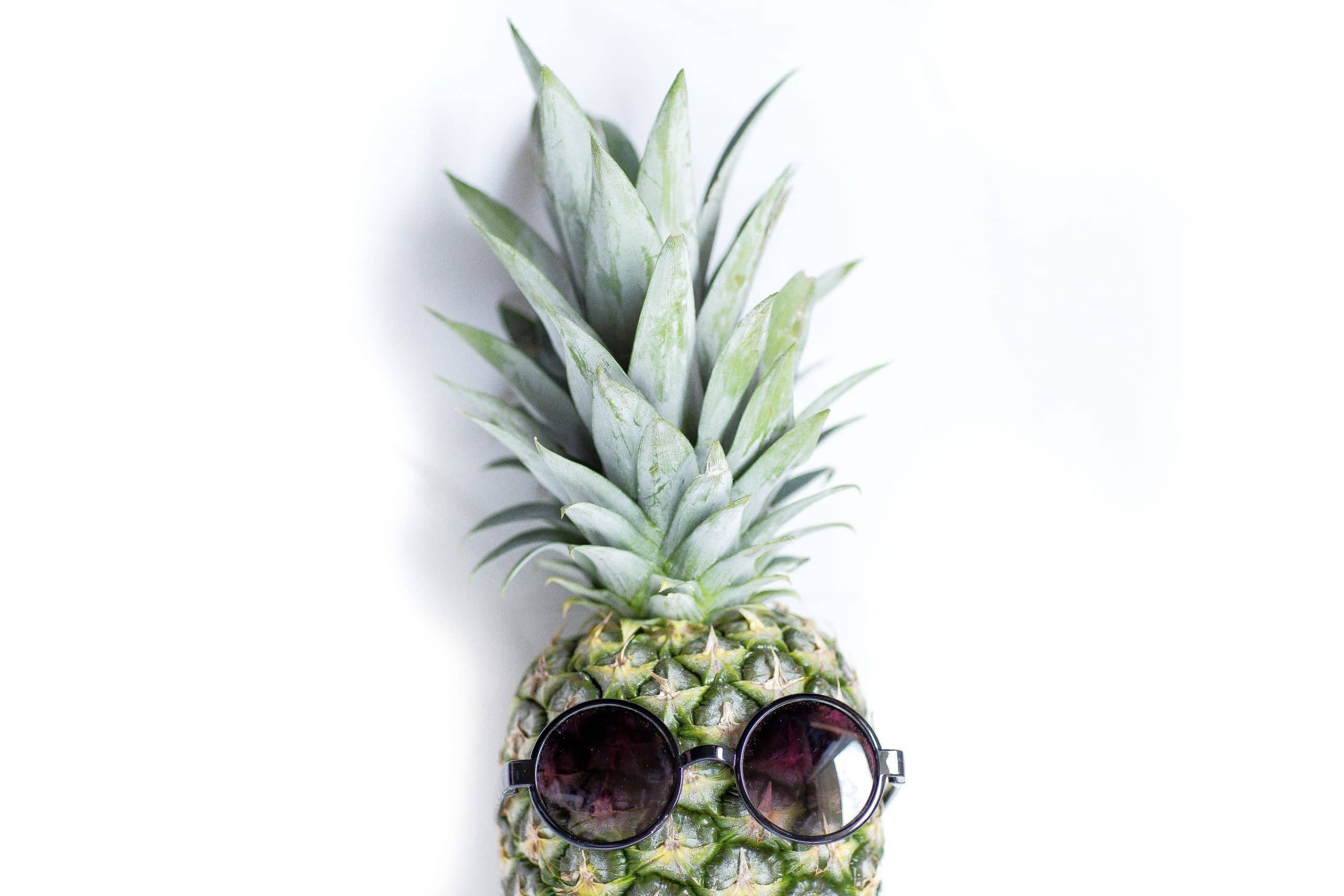 Pineapple with sunglasses on ready to be put into a fermented recipe