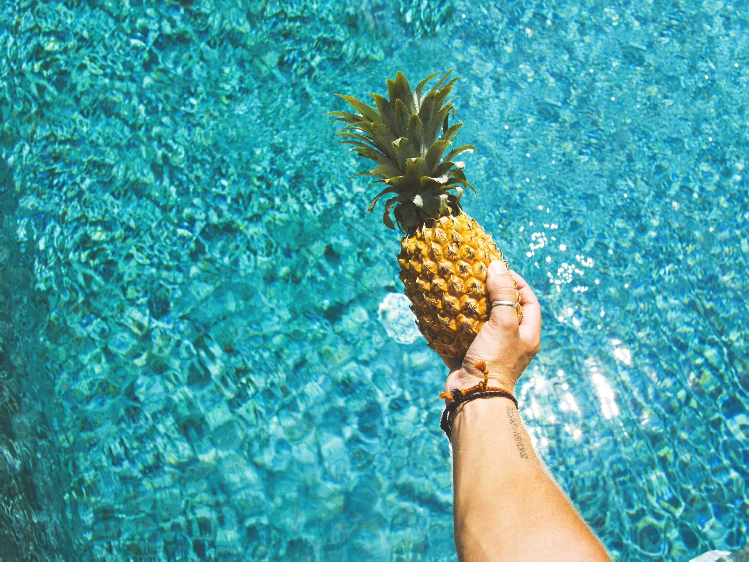 Holding a pineapple over water preparing for fermentation recipes